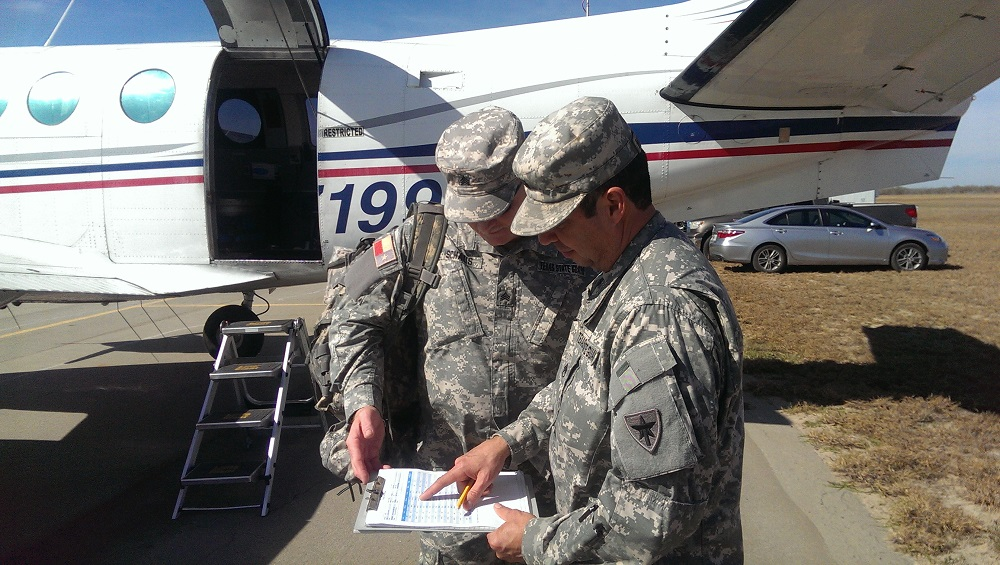 Sgt. Stephen Schaus, 3rd Battalion, 1st Regiment, Texas State Guard, reviews the daily flight plan and the amount of bait to be dropped with Staff Sgt. Joel Hernandez, 3rd Battalion, during the aerial rabies vaccine bait distribution over the Zapata-based Border Maintenance Zone during the Oral Rabies Vaccination Program, sponsored by the Texas Department of State Health Services Zoonosis Control Branch, January 10, 2018.    (Texas State Guard photo by Capt. Stephen Walker)