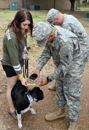 In an Emergency Tracking Network system exercise in Huntsville, Texas, Pfcs. James Little and Lee McWilliams, 2nd Battalion, 8th Regiment, Texas State Guard, scan an ETN band attached to the collar of a dog, February 24, 2018.  The system would track the dog's location to a designated pet shelter during an emergency or disaster so that the pet can be located by the pet owner.  (Texas State Guard Photo by Cpl. Christopher Feriante)