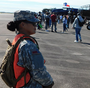 Pvt. Mary Jane Moore, 8th Regiment, Army Component, Texas State Guard, stands at a flight line to guide visitors, who are looking at the collection of commemorative aircraft, safely away from the active ramps and taxiways where aircraft are moved and refueled at the Commemorative Air Force Wings Over Houston Airshow at Ellington Airport, Houston, Texas, October 19, 2018. (Texas State Guard photo by Staff Sgt. Gregory Illich)