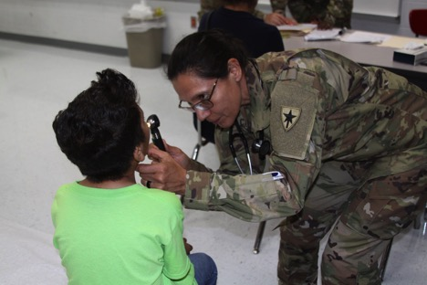 CPT Adrian Cano, a Texas State Guard physician, gives a nine-year old boy a much-needed basic health care examination during Operation Lone Star at the Mission MPOD, Mission, Texas.