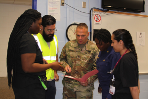 Brig. Del Marco Coppola, DO, discusses a patient's case with members of the multi-agency staff, including a doctor from Mexico, nursing students and a provider form the U.S. Public Health Service during operation Lone Star 2019 at the Brownsville MPOD, Brownsville, Texas.